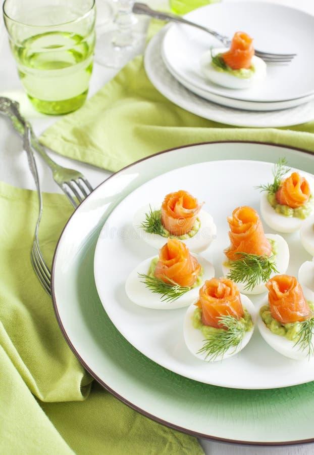 Huevos rellenos con el relleno y el salmón ahumado del aguacate imagen de archivo libre de regalías