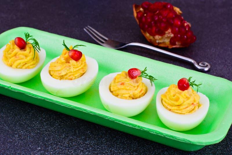 Huevos rellenos sabrosos con la granada imagenes de archivo