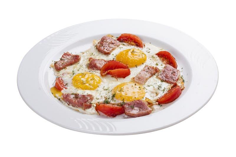 Huevos revueltos con el jam?n y los tomates en una placa blanca imagen de archivo libre de regalías