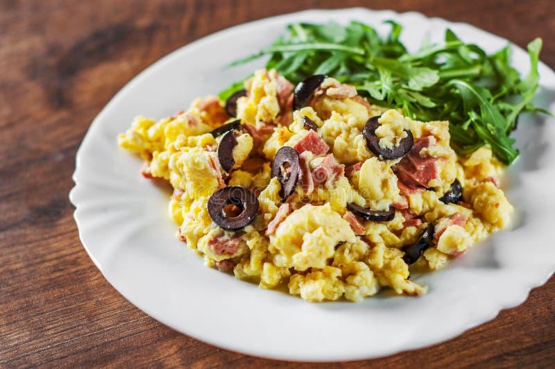 Huevos revueltos con la ensalada del jamón, de la aceituna y del arugula en la placa blanca en la tabla de madera foto de archivo