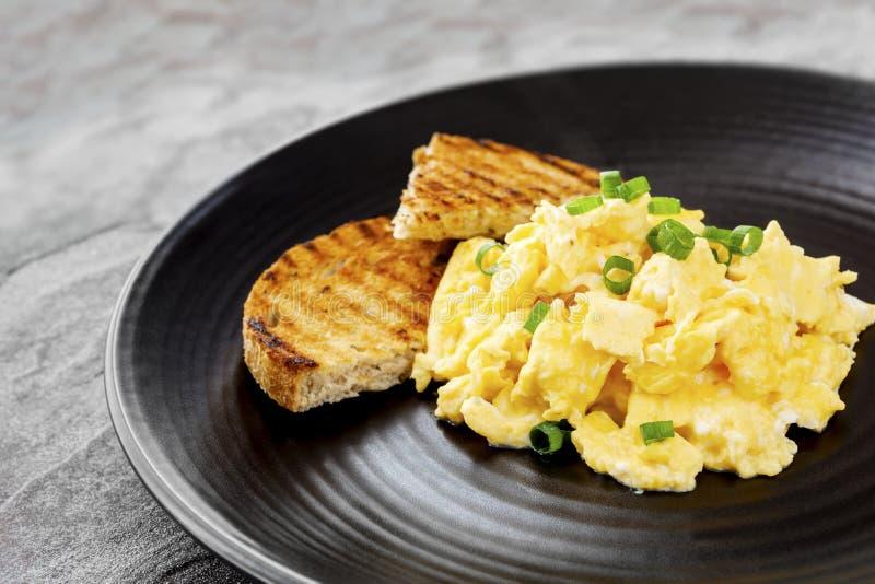 Huevos revueltos con la tostada en la placa negra imagenes de archivo