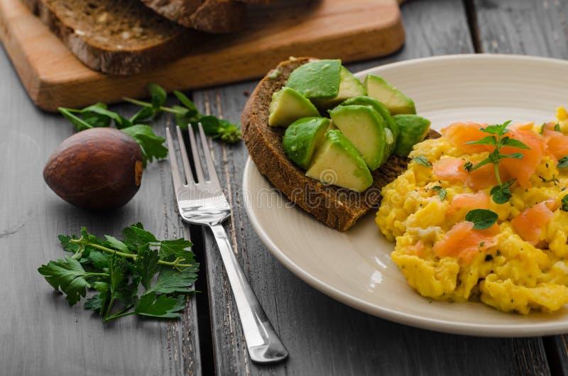 Huevos revueltos y tostada de color salmón del aguacate foto de archivo