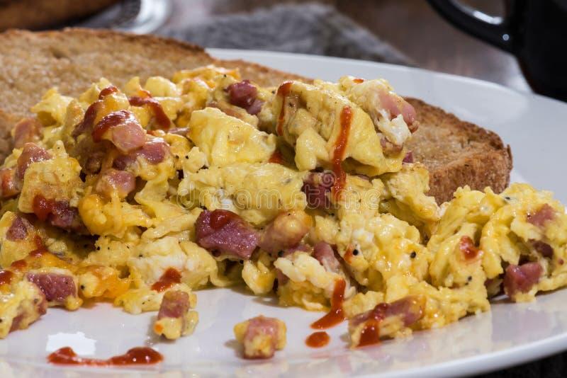 Huevos revueltos y tostada del desayuno fotos de archivo