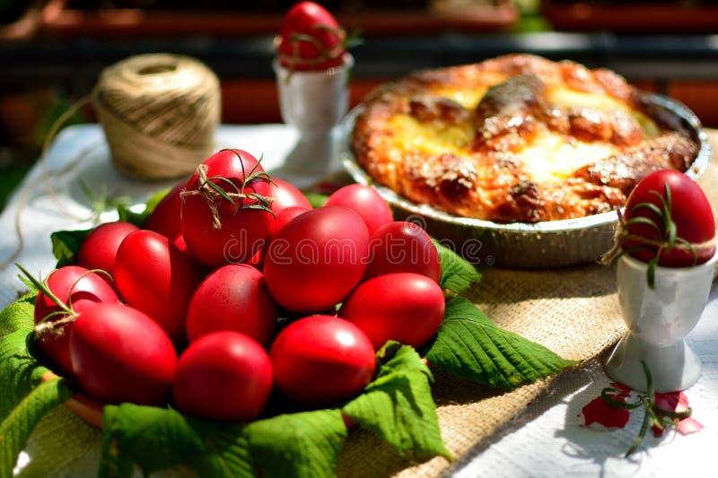 Huevos rojos de Pascua y pan dulce foto de archivo