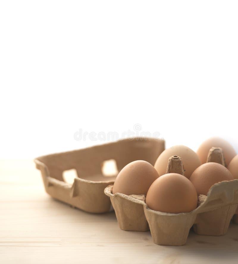 Huevos sobre Wodden y el fondo blanco fotos de archivo libres de regalías