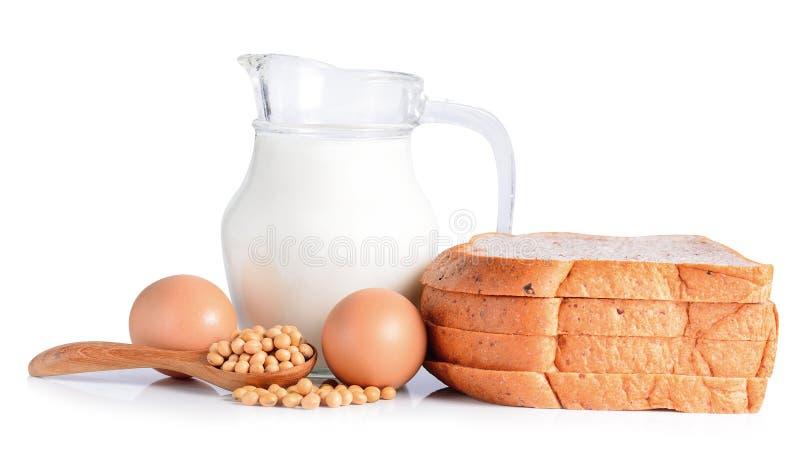 Huevos, sojas, leche y pan en el fondo blanco foto de archivo