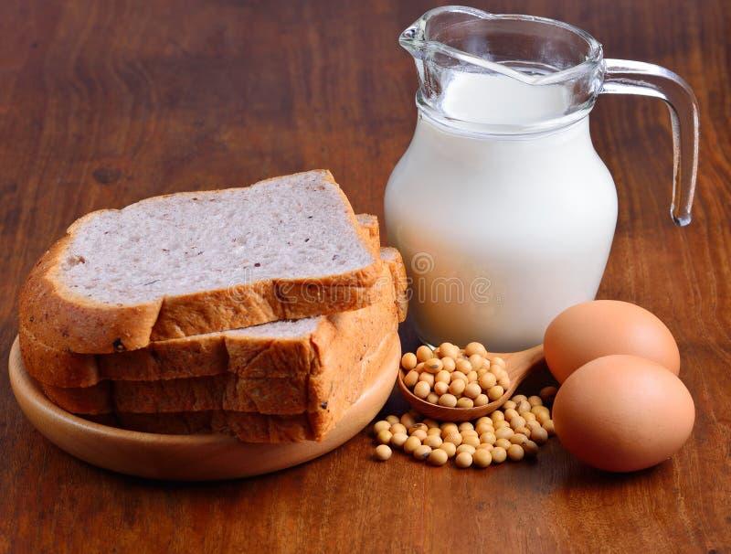 Huevos, sojas, leche y pan en fondo de madera imágenes de archivo libres de regalías