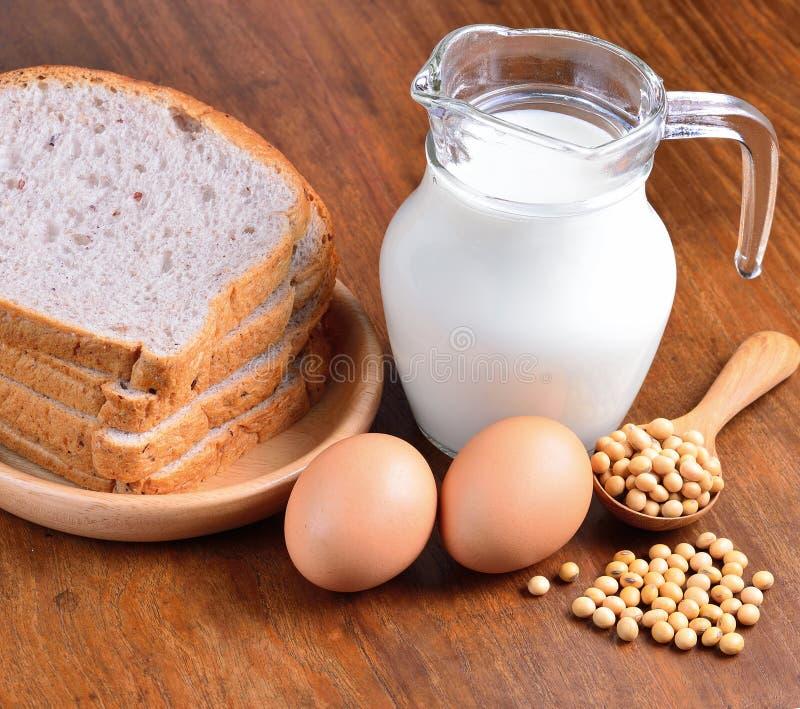 Huevos, sojas, leche y pan en fondo de madera foto de archivo libre de regalías