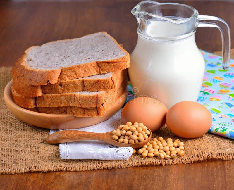Huevos, sojas, leche y pan en fondo de madera imagen de archivo