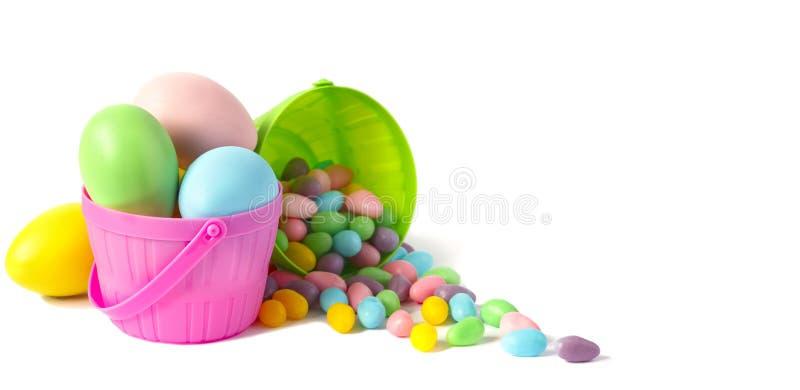 Huevos y caramelo de Pascua en cestas coloridas en el fondo blanco imagen de archivo