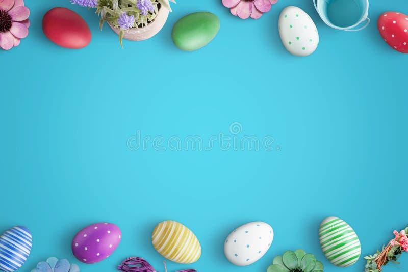 Huevos y flores de Pascua en superficie azul Endecha plana, escena de la visión superior con el espacio libre para el texto imagen de archivo