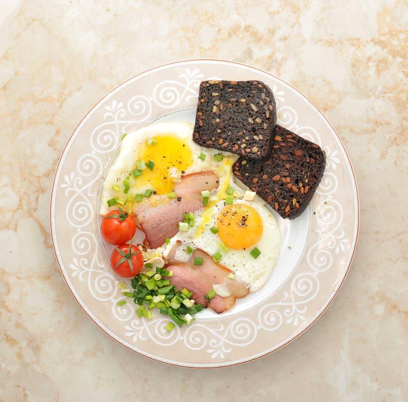 Huevos y tocino con pan tostado, tomates y cebollas verdes imagen de archivo libre de regalías