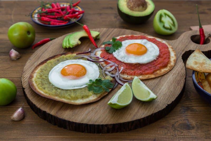 Huevosdivorciados, heerlijk voedsel met eieren, verse salade en kruiden kruidige herby saus stock foto