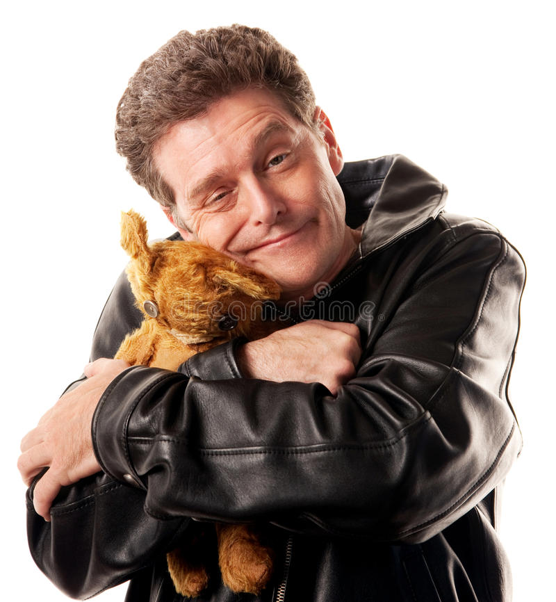 Hug a Toy. Caucasian man in leather jacket hugs a brown bear royalty free stock image