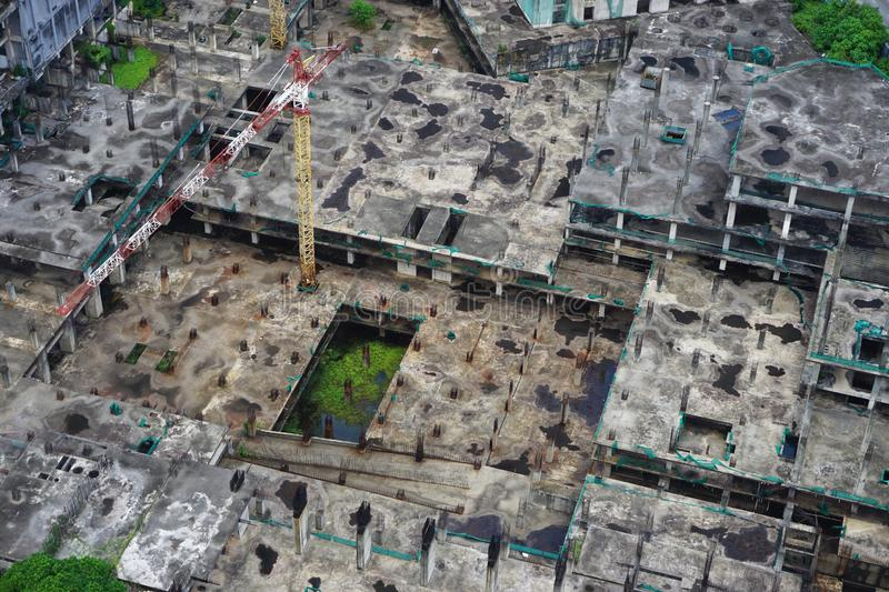 Huge abandoned construction project in Southeast Asia. Vast concrete construction site left in ruins in Southeast Asia. A crane is in place to prepare for stock photos
