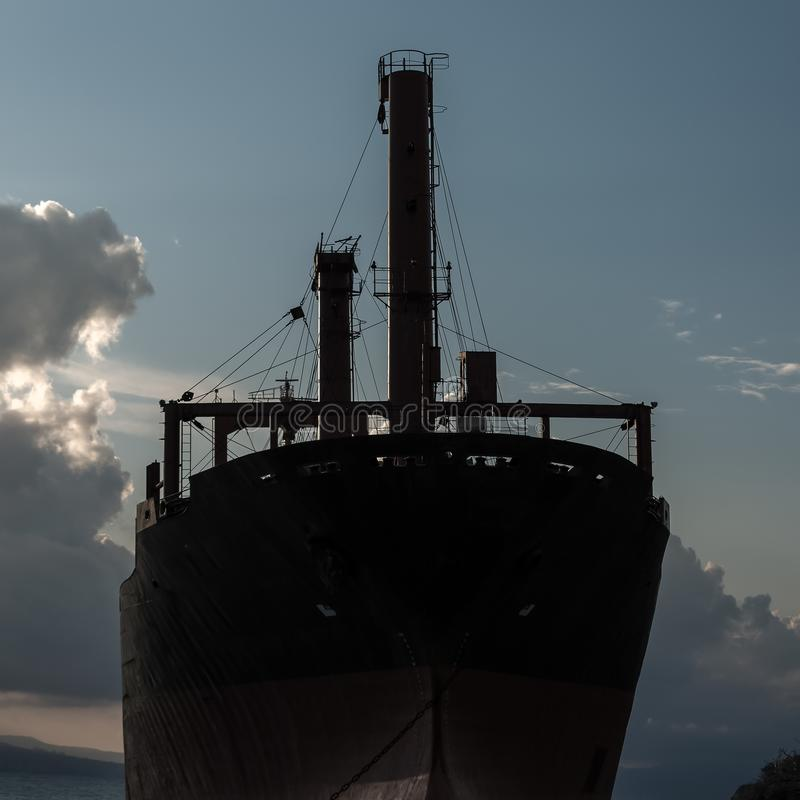 A huge  ship thrown on the black sea coast close-up at sunset stock photography