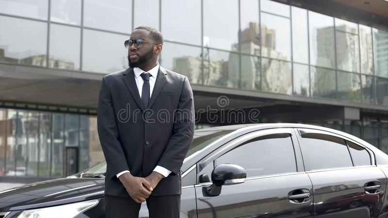 Huge Afro-American security chief monitoring order outside business center stock image