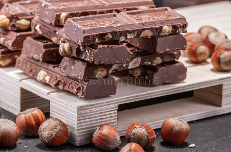 Huge of chocolate with whole hazelnuts. On the pallet .Brown tonality. stock image