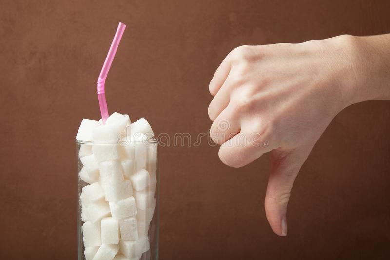 A huge amount of sugar in juice or soda drinks. Sugar cubes in glass and hand shows thumbs down.  stock photos