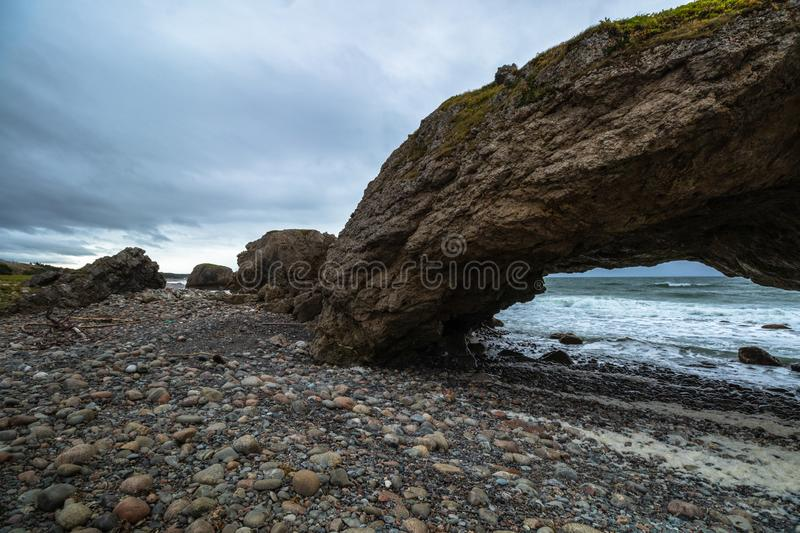 Stormy evening at arches in Shallow Bay Newfoundland. Huge arches line the beach at the Arches Provincial Park in Newfoundland. Dolomite rock structures formed royalty free stock photos