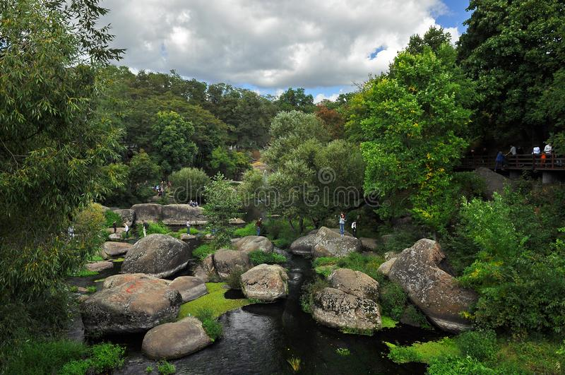 Huge boulders lie in the river among high green trees against the blue sky. Journey nature stone flowing landscape water destination tourism forest surrey uk royalty free stock photo