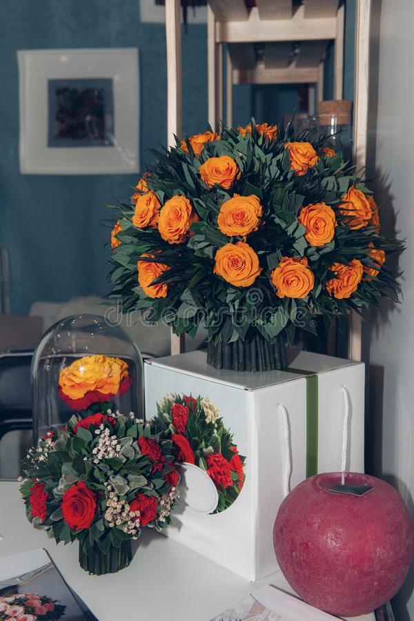 A huge bouquet of beautiful orange roses decorated in the interior on a white bedside table royalty free stock image