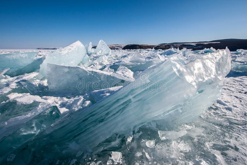 Huge broken pieces of ice frozen into the ice of Lake Baikal glisten in the sun. Blue sky without clouds. Hills on the horizon stock photography