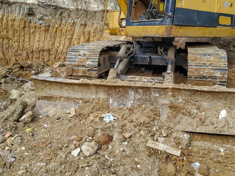 Huge bulldozer excavator of working among the dirt and mud of excavation site while digging on the construction place stock image