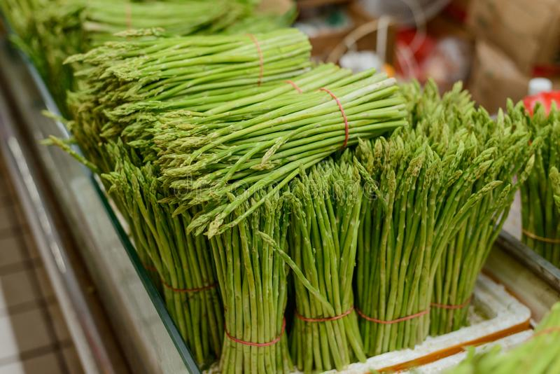 Huge bunches of asparagus. Huge bunches of long asparagus stems. Fresh vegetables and greenery for sale stock photos