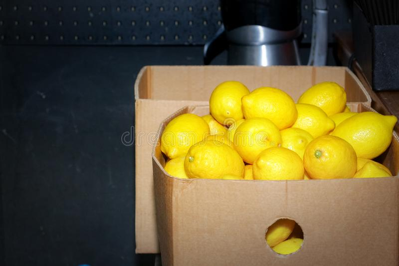 A huge cardboard box to the top filled with lemons on a dark background stock photography