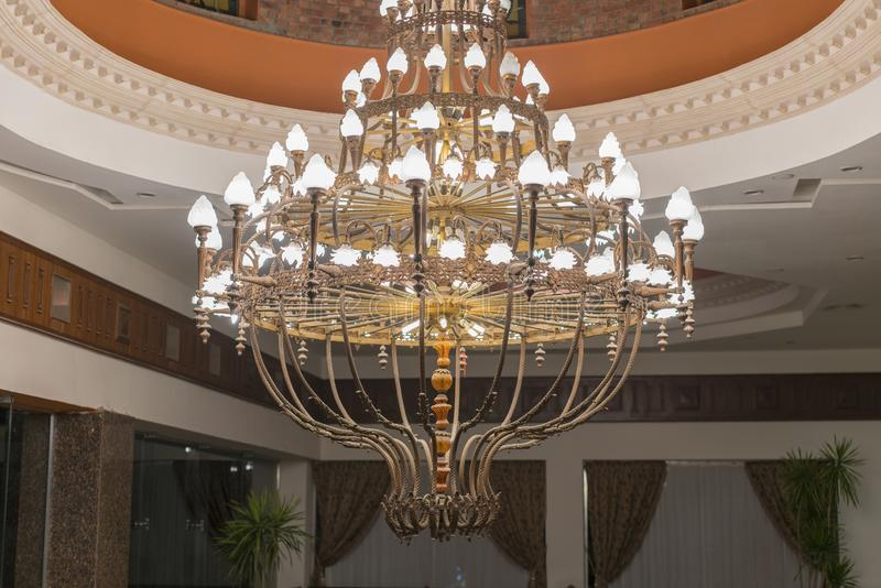 Huge chandelier in the hall. Chandelier on decoarted ceiling of a ballroom royalty free stock image