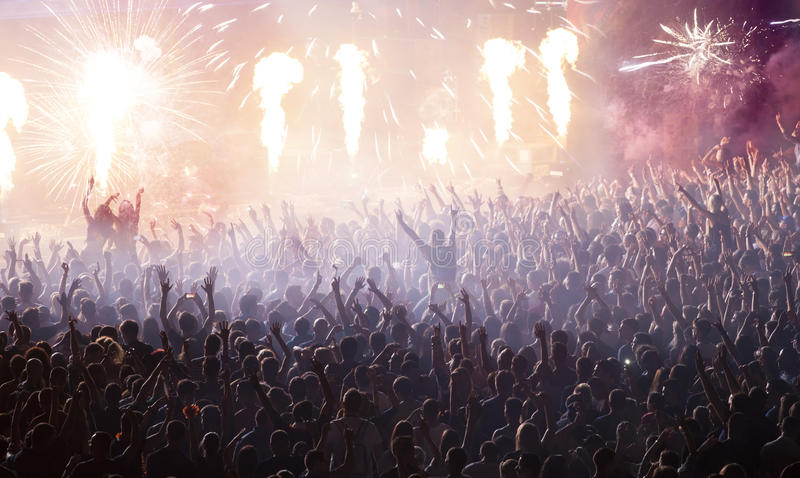 Huge cheering crowd at concert. Cheering crowd at concert in front of stage with pyrotechnics stock image