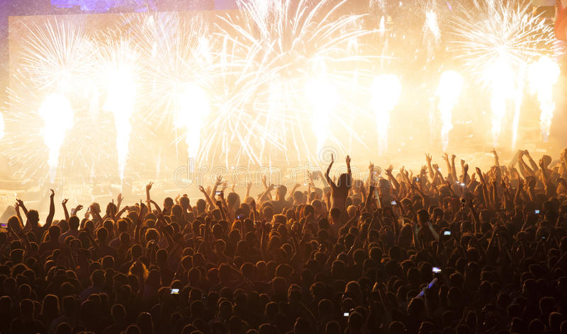Huge cheering crowd at concert. Cheering crowd at concert in front of stage with pyrotechnics stock photos