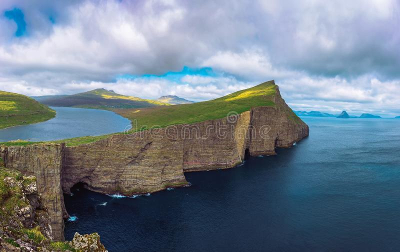 Huge cliff and lake Sorvagsvatn on island of Vagar, Faroe Islands, Denmark. Panorama of the cliff Traelanipan and lake Sorvagsvatn located on the island of stock photos