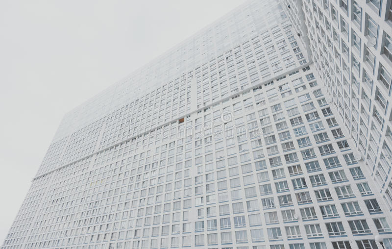 Huge contemporary white and grey residential skyscraper apartment building. With multiple regular windows on facade, Moscow, bright cloudy day, view from bottom stock photography