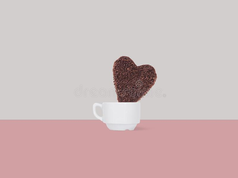 A huge cookie from ground coffee in the form of a heart in a coffee cup on a colorful background stock photo