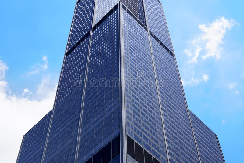 Huge corner of the Modern office building. Low angle shot of Skyscrapers. Modern office building. Skyscraper close-up. A low angle view. White clouds in the sky royalty free stock image