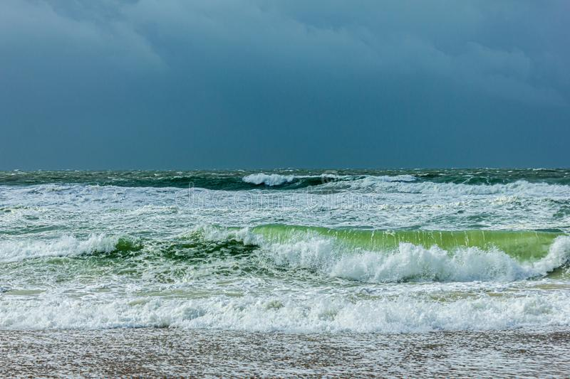 Huge crashing rolling waves on the beach with choppy sea on the background during a massive storm under a dark sky.  royalty free stock image