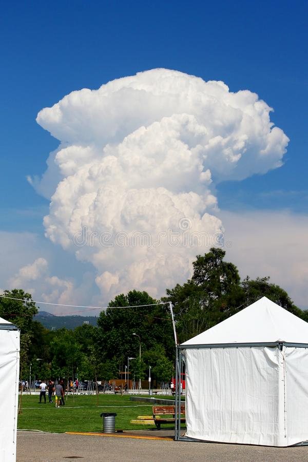 Huge cumulus cloud rising high in the blue sky royalty free stock image