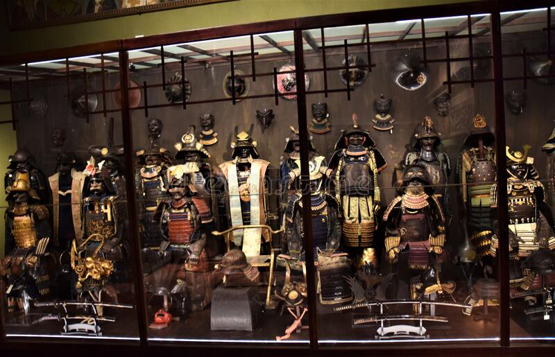 A huge display case contains dozens of wonderful and ancient samurai costumes with swords and shields, in a room of Villa Stibbert stock photo