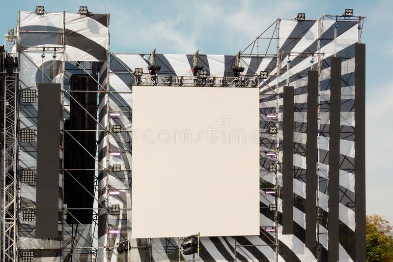 Huge display and loudspeakers on metal frame construction under blue sky. Mockup of screen or information panel installed outside royalty free stock photo