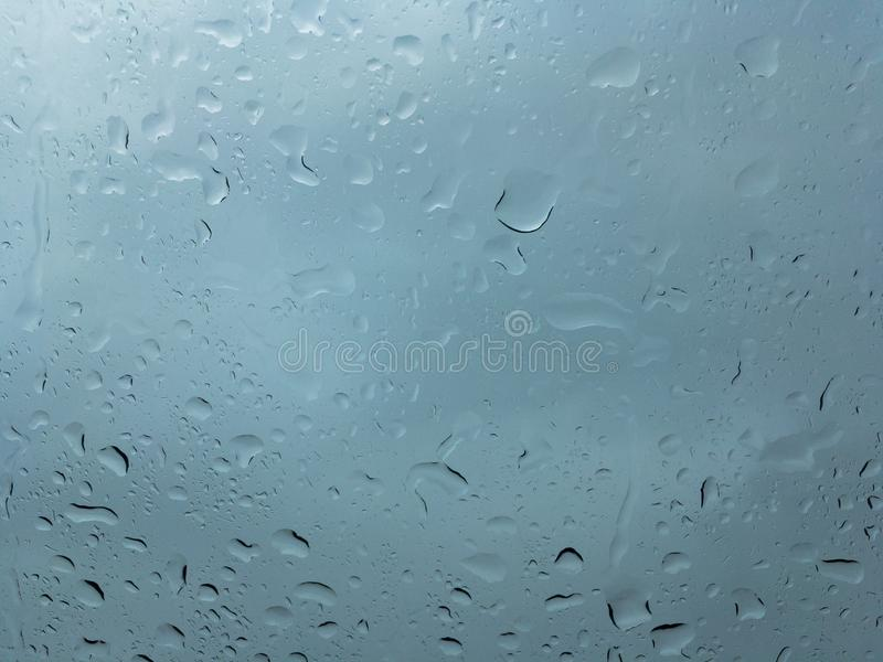 Huge drops of rain on clear glass. Huge drops of rain on glass, rain drops on clear glass roof of a car royalty free stock images