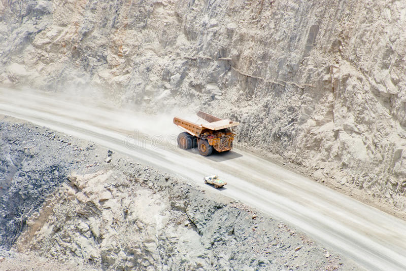 Huge dump truck moving downhill passing normal car. David and Goliath: huge mining dump truck passing little normal car. those machines are used for carring tons royalty free stock photo