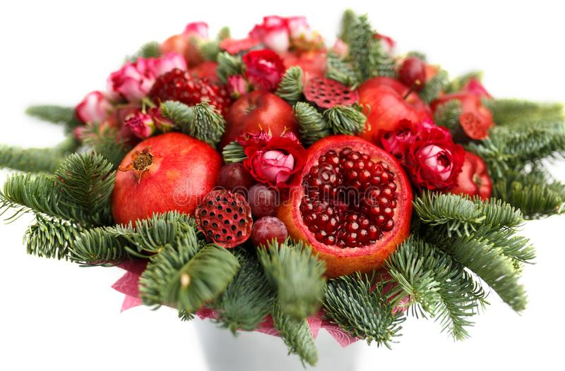 Huge edible fruit bouquet consisting of pomegranates, apples, grapes, rose flowers and fir twigs on white background royalty free stock images