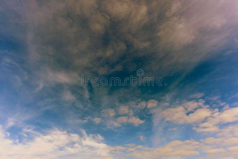 A huge, endless sky, illuminated by the rising sun. Pink, blue, white fluffy clouds in summer time royalty free stock images