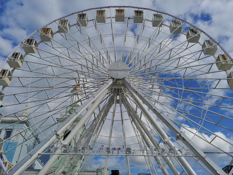 Huge Ferris wheel at city center. entertainment for adults and children. blue sky with clouds on background. low angle image stock photo