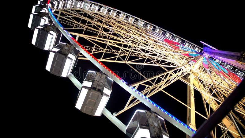 Huge Ferris wheel with illuminated passenger cars, amusement ride in Paris royalty free stock photos