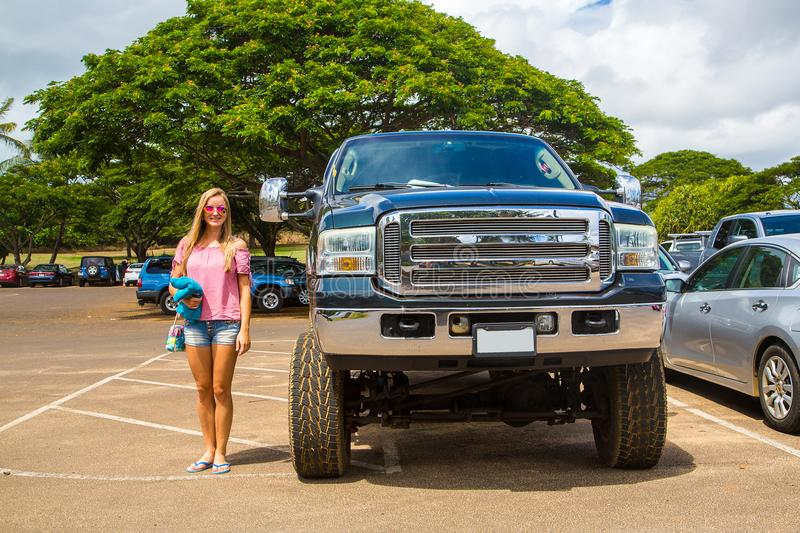 Huge Ford monster truck in comparison to a young lady royalty free stock photography