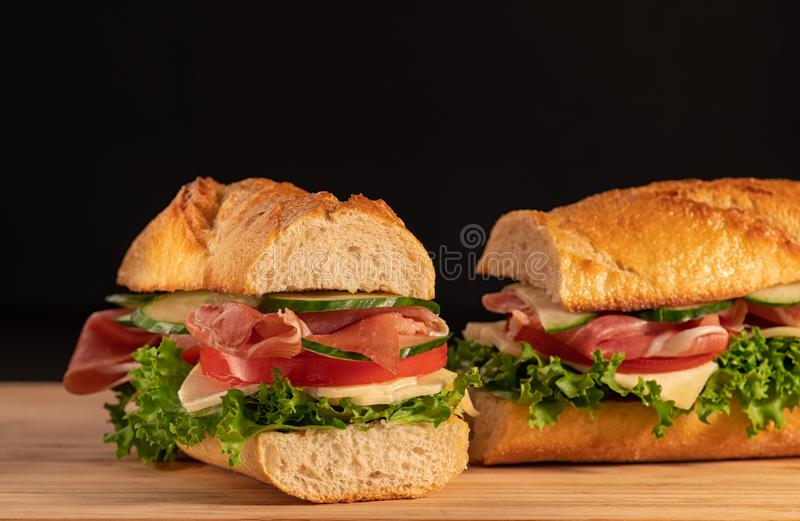 Huge fresh crispy baguette sandwich with meat, prosciutto, cheese, lettuce salad and vegetables. Close up. Black background. Space royalty free stock image