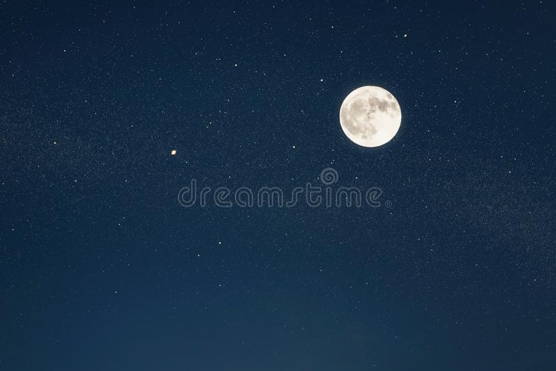 Huge full moon on the night sky with bright stars. stock photography